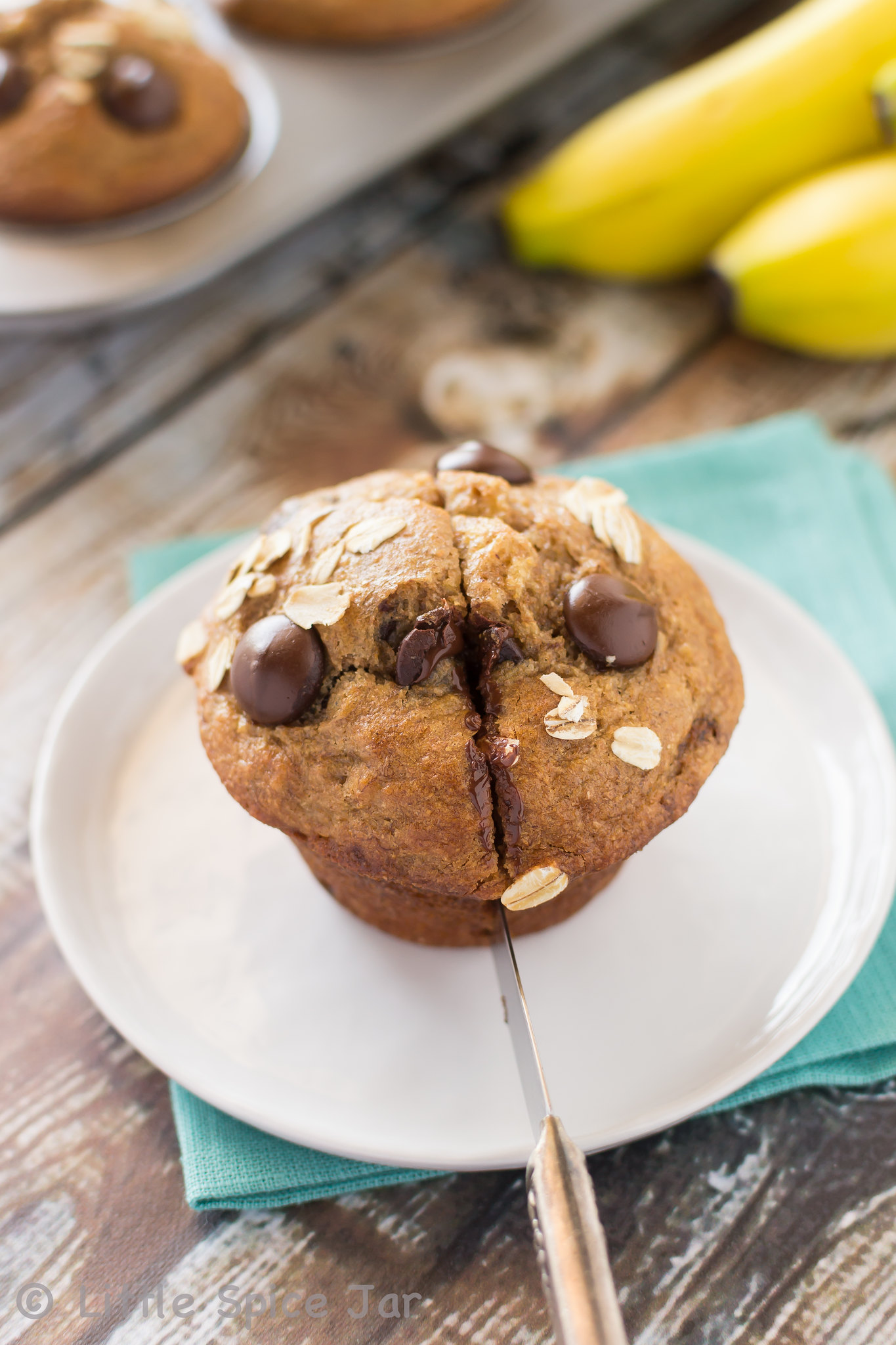 chocolate chip muffin slicing with knife on white plate