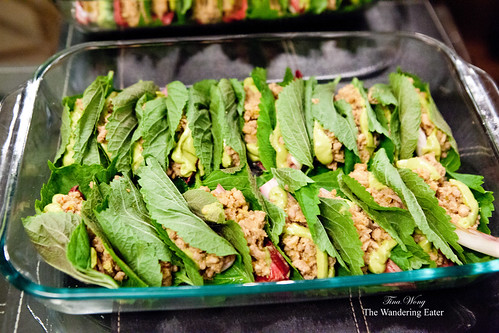 Ssam (Korean style wrap) of pork, endive, red onion, avocado sauce wrapped in shiso leaf