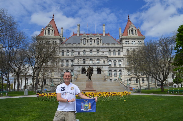 Ryan Janek Wolowski waving the state flag of New York at the The New York State Capitol building a National Historic Landmark on the Empire State Plaza in the capital city of Albany, NY, USA