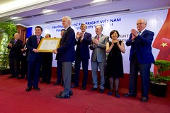 U.S. Secretary of State John Kerry applauds as former U.S. Senator Bob Kerrey - Chairman of the Board of Trustees of the new Fulbright University Vietnam - is presented with the school's license during a ceremony on May 25, 2016, at the Rex Hotel in Ho Chi Minh City, Vietnam. [State Department photo/ Public Domain]
