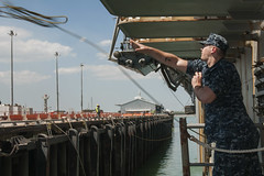 Seaman Jeremiah Baker throws a messenger line to the pier as USS Bonhomme Richard (LHD 6) arrives in Darwin, Sept. 8. (U.S. Navy photo by Mass Communication Specialist 3rd Class Michael Achterling)