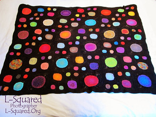 Completed blanket laying out flat on a white sheet.