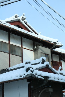 old style home with snowy eaves
