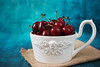 Fresh cherries in a white bowl, a large cup. Blue background. Rustic style