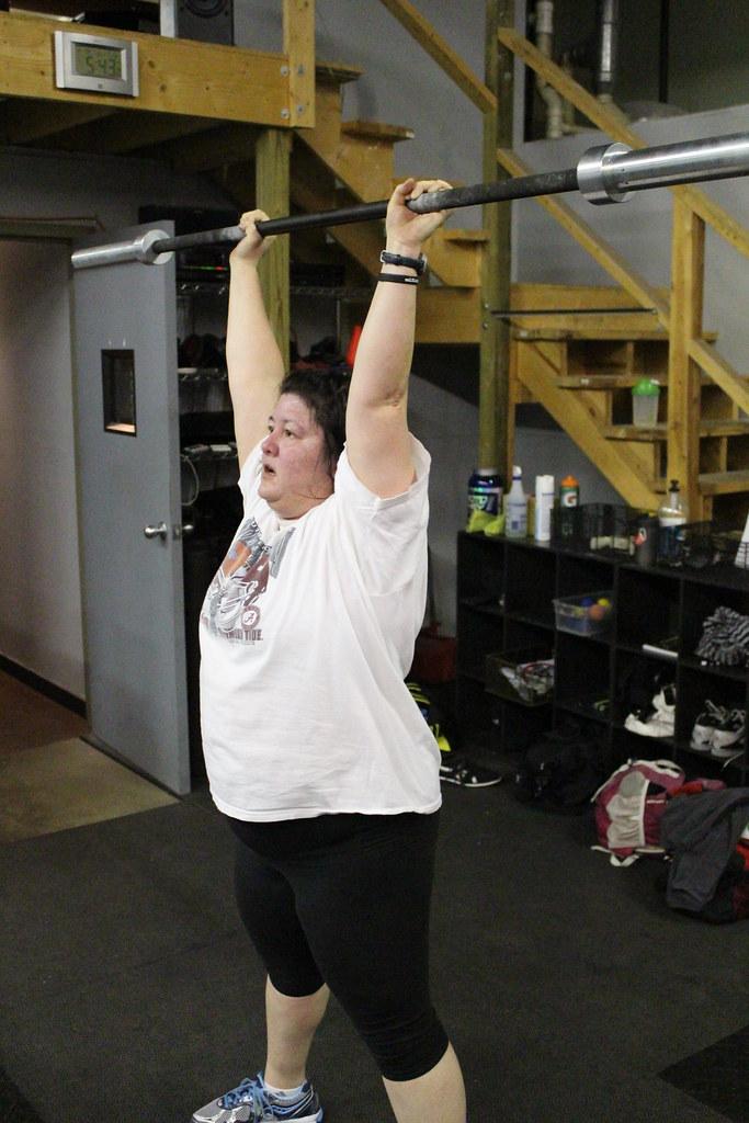 バーベルを頭上に掲げて肩のトレーニングをする太った女性