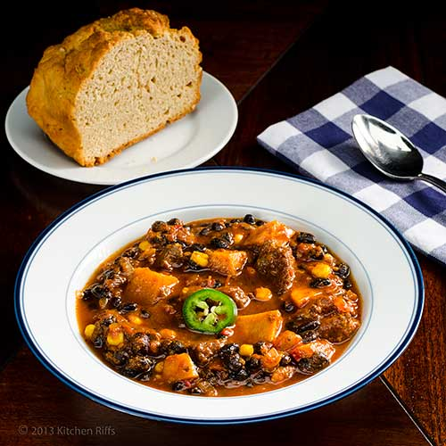 Chunky Pork and Sweet Potato Chili in bowl, with bread in background