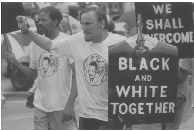 "A civil rights march where black and white men hold signs that say ""black and white together"""