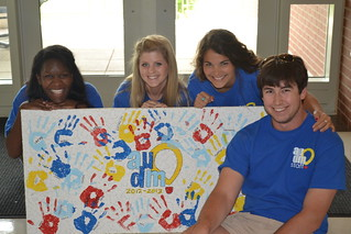 Students pose by a hand-painted sign.