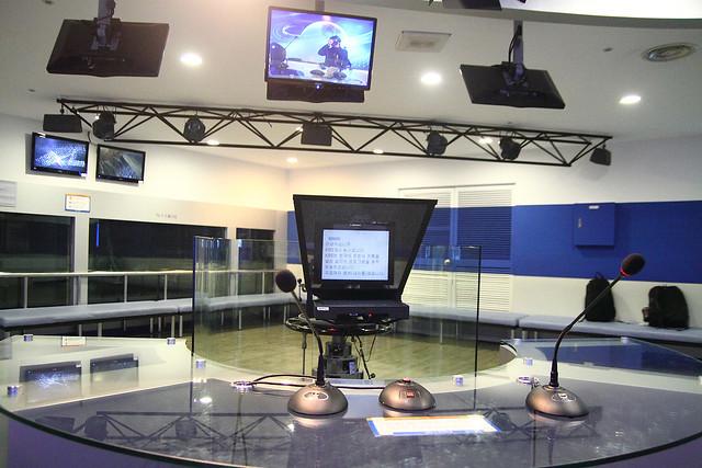 录影机前显示的新闻稿,主播可以看着镜头同时