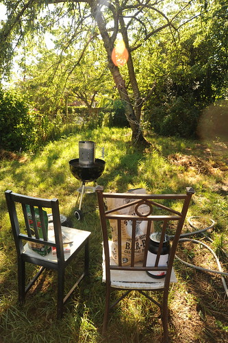 Preparing for the Sur offering, two old chairs, hose, charcoal grill, starter chimney, charcoal, wood, container, back yard that used to be three large chicken coops, grass, cherry tree, Seattle, Washington, USA by Wonderlane