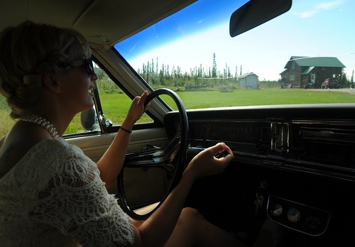 Jessie arrives at her house, wearing a lace dress, pearls, sunglasses, driving Chris's vintage car, Wedding of Jessie and Chris, Fairbanks, Alaska, USA by Wonderlane