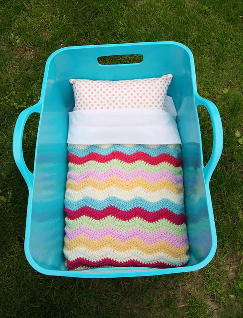 Doll's bed with ripple blanket