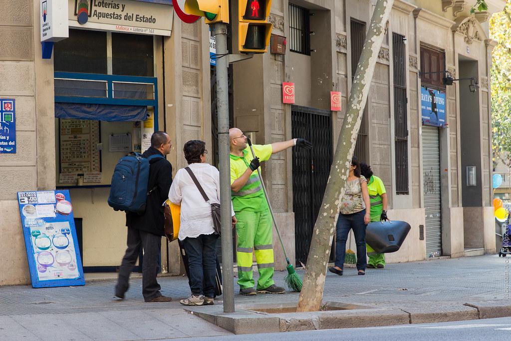 Уборщик показывает дорогу туристам в Барселоне