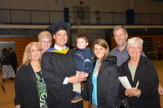 A graduate student at Commencement with his family