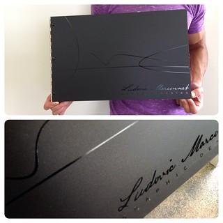 Custom matte black acrylic graphic designportfolio book with vinyl decal treatment