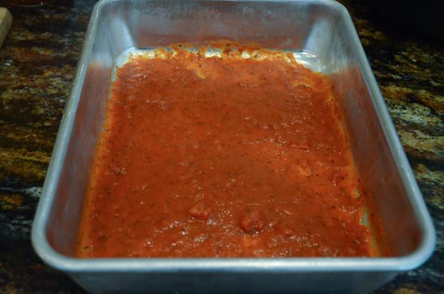 A deep pan has marinara sauce added.
