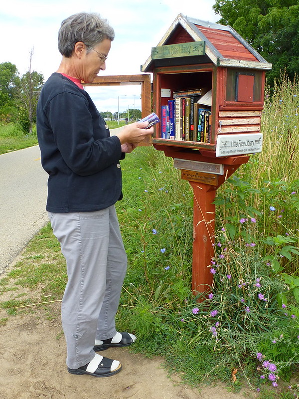 Catherine looking at a book at one of many Little Free Libraries in Madison, Wisconsin