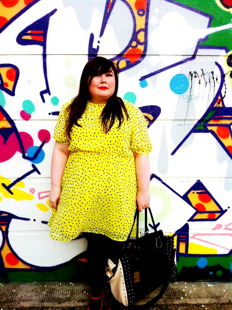 Me wearing a yellow patterned dressagainst a graffiti backdrop