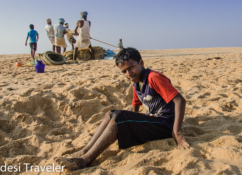 boy and fishermen on beach Kerala