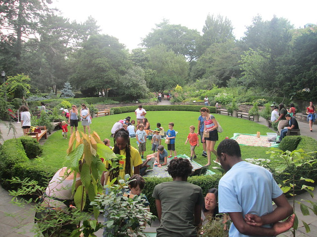 Families visit hands-on stations during a Discovery workshop in the Fragrance Garden. Photo by Ashley Gamell.