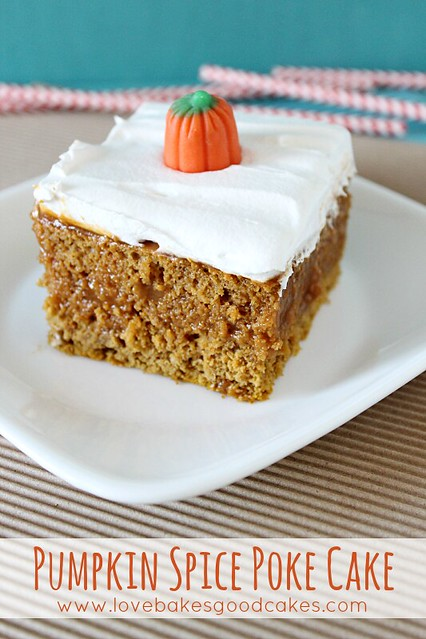 Pumpkin Spice Poke Cake on a white plate with a candy pumpkin on top.