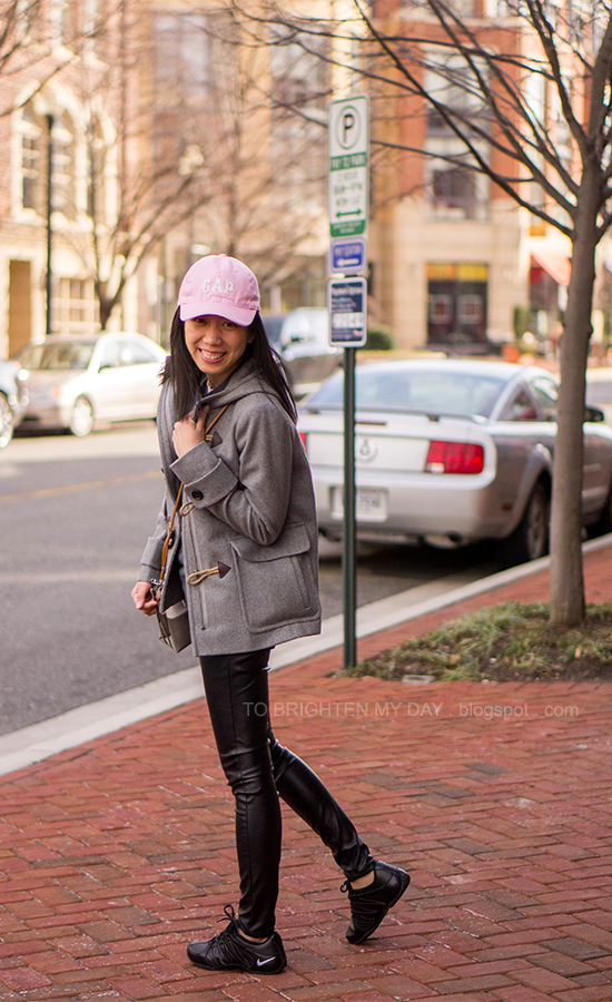 pink cap, gray toggled coat, colorblocked striped crossbody bag, faux leather pants, black sneakers
