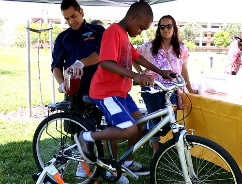 To enjoy nutritious fresh fruit smoothies - Summer Food kickoff participants power a blender using a stationary bicycle.