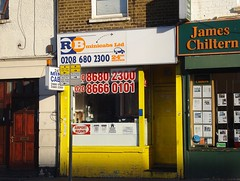 "The same shopfront as above, still the same colour and with the same phone numbers in the window, but now the sign reads ""RB Minicabs Ltd"" and the intercom has been removed."