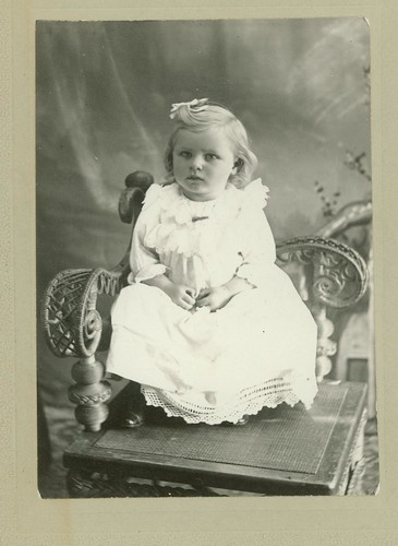 Small girl in square chair with rattan