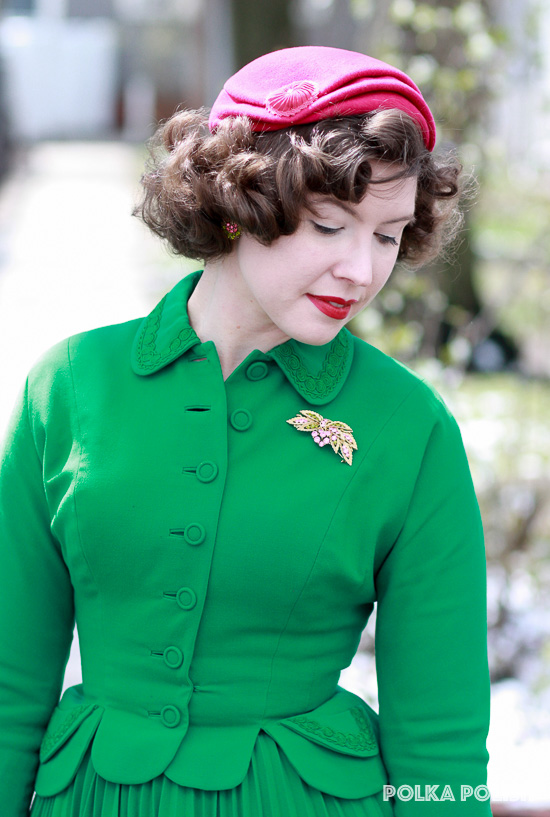 Soutache collar detailing on a bright green Don Loper suit paired with a goldtone rhinestoned brooch set and a bright pink close hat with matching rhinestones
