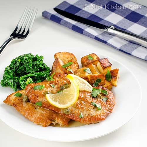 Turkey Piccata with lemon and parsley garnish, on plate with vegetables