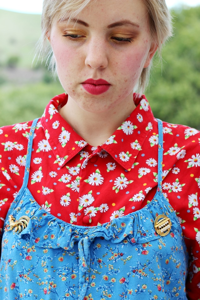gold eye makeup, blue floral over red floral, gold brooches