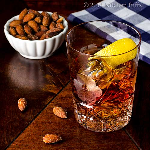 The Vieux Carré Cocktail in glass with lemon twist garnish, bowl of nuts in background