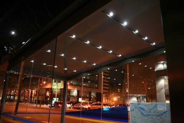A prototype of the new STM bus shelter at night, with lighting