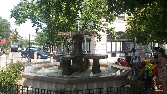 children throwing coins in the Giddings Plaza fountain