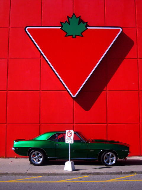 Red & Green: A 1969 Chevy Camaro under a giant Canadian Tire logo.