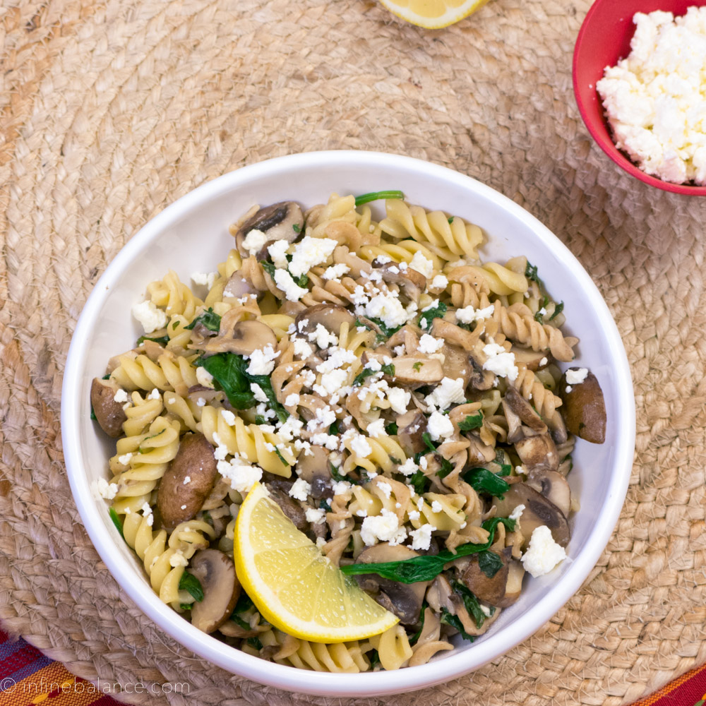 while bowl with fusilli pasta, mustrooms and feta cheese. served with a lemon wedge