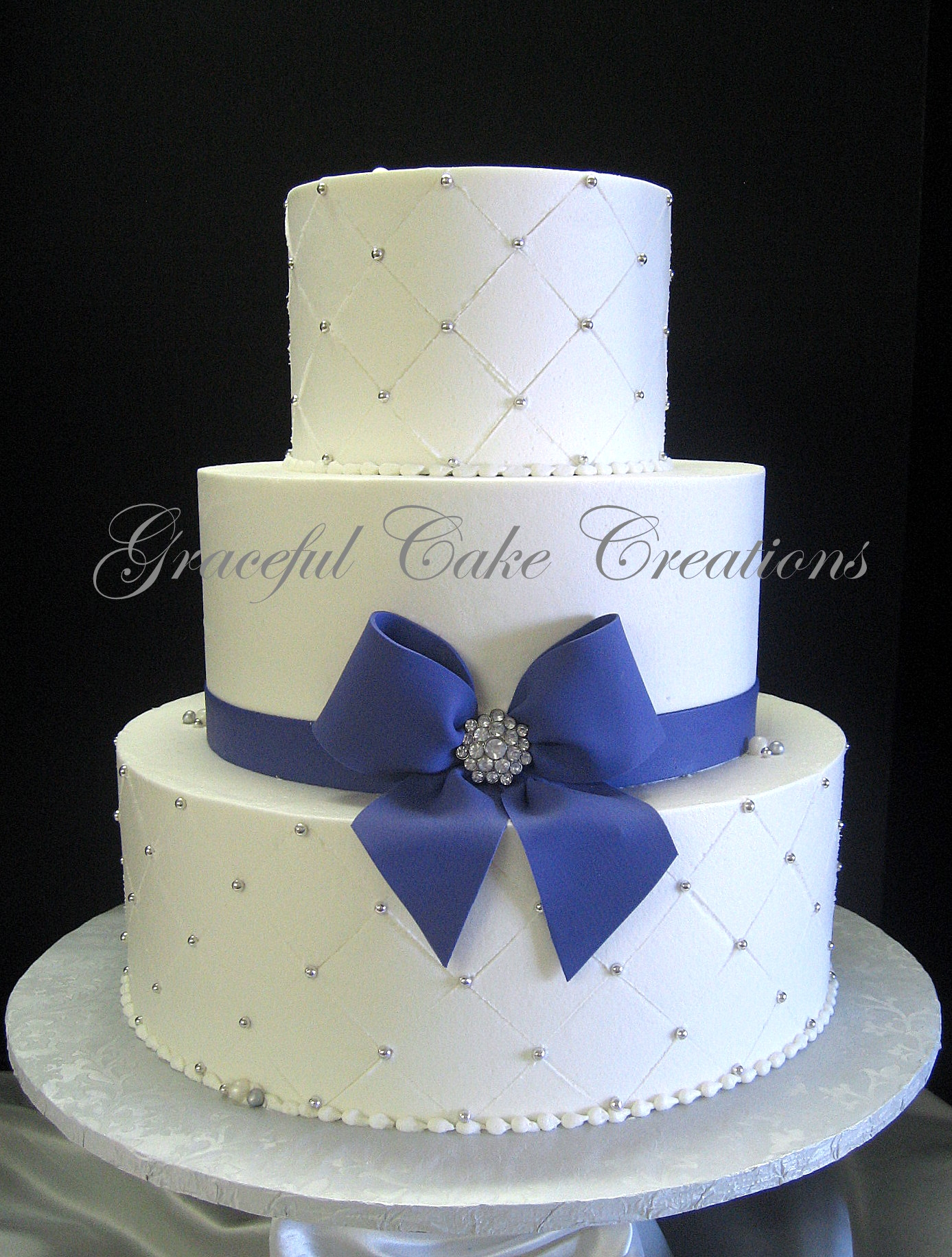 Elegant White Wedding Cake with Purple Ribbon and Bow with