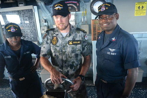 Royal Australian Navy Leading Seaman Adam Doolan (center) takes the helm on board USS Chung-Hoon (DDG 93)