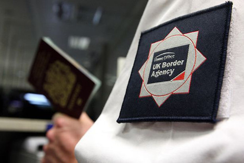 UK Border Agency officer checking a passport in the North Terminal of Gatwick Airport-811706