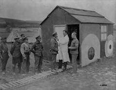 A Canadian dentist outside his hut attending to patients / Dentiste canadien à l'extérieur de sa baraque, en train d'examiner des patients