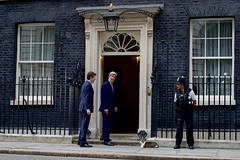 U.S. Secretary of State John Kerry, escorted by Special Adviser to the Prime Minister Nigel Casey, laughs after looking at a cat outside No. 10 Downing Street in London, U.K., on June 27, 2016, before entering to speak with Cameron following a meeting with the Secretary's counterpart, British Foreign Secretary Philip Hammond, in the aftermath of last week's 'Brexit' vote by the British people. [State Department Photo/ Public Domain]