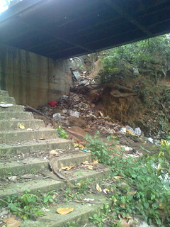Garbage strewn across the bridge steps that lead to the river