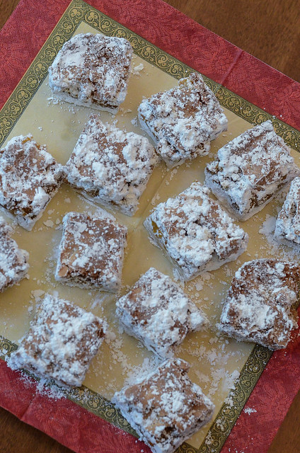 Apricot Bars dusted with powdered sugar on a napkin shot from over the top.