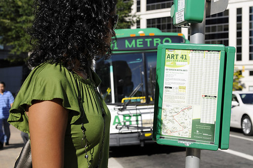 Young woman studying bus schedule. Downloaded from CommuterPageBlog by busboy4