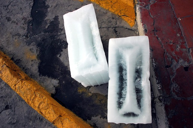 Art comes in pieces: 2 blocks of ice melting on the street, string, wet concrete, rough and smooth, lines, orange, red, gray, white, Mazatlan, Mexico