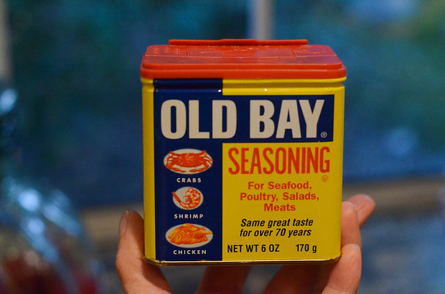 A hand holds a container of Old Bay Seasoning.