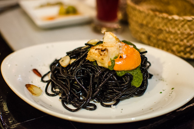 A beautiful plate of squid ink pasta topped with fried garlic and scallop at Sevilla's Vinería San Telmo.
