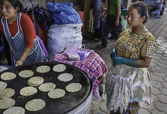 Woman with green hands buying tortillas at Antigua market