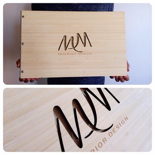 Custom interior design portfolio book with cut-out and engraving treatment on amber bamboo